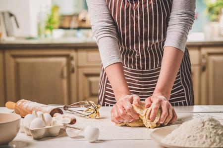 Vrouw handen kneden deeg op de keuken tafel. Een vrouw in een gestreepte schort kookt in de keuken