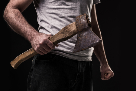 A man holds an ax in his hands against on black background. Criminal 版權商用圖片 - 78406983