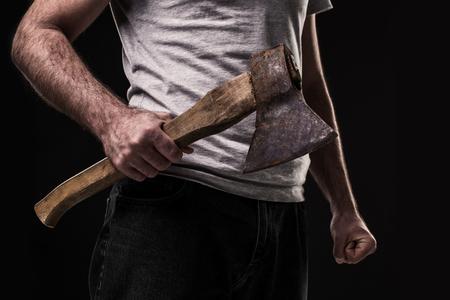 Een man houdt een bijl in zijn handen tegen op zwarte achtergrond. crimineel