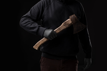 violation: A man in gloves holds an ax in his hands against a black background. Criminal