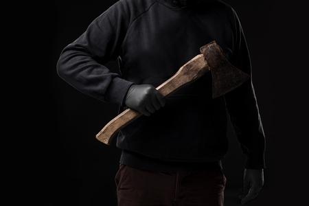Een man in handschoenen houdt een bijl in zijn handen tegen een zwarte achtergrond. crimineel