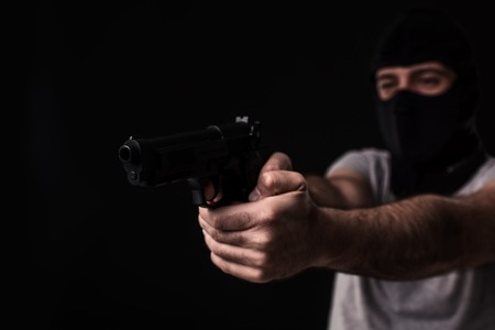 The robber in a mask with a gun pointed to the side on a black background