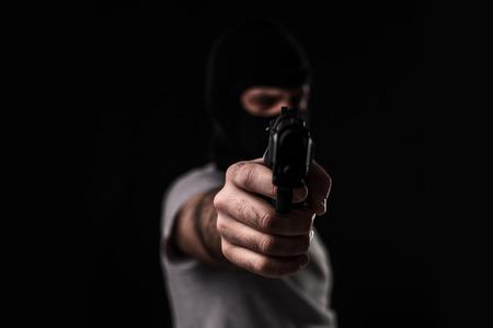 黒の背景にカメラに銃を目指すと覆面をした強盗