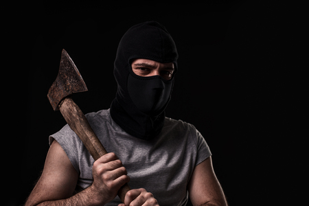 Bandit in black mask with hatchet on black background