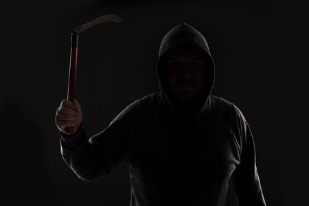 swindled: Criminal in dark clothes and balaclava with scythe Stock Photo