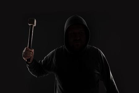 delincuencia: Criminal en ropa oscura y pasamontañas con martillo
