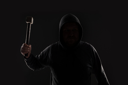 Criminal in dark clothes and balaclava with hammer Stock Photo