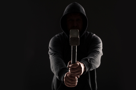 swindled: Criminal in dark clothes and balaclava with hammer Stock Photo