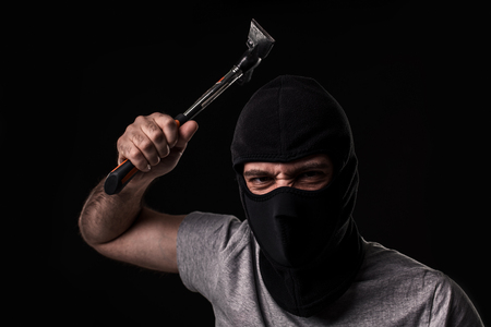 swindled: Criminal in T-shirt and balaclava with hammer