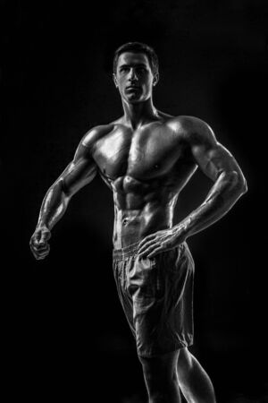 Muscular and fit young bodybuilder fitness male model posing ove