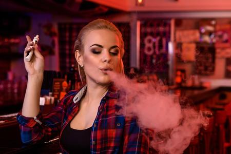 De jonge mooie vrouw rookt een elektronische sigaret bij de vapebar