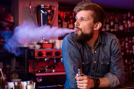 Vape. Vaping man in een dampwolk. Foto wordt genomen in een vape bar. Stockfoto