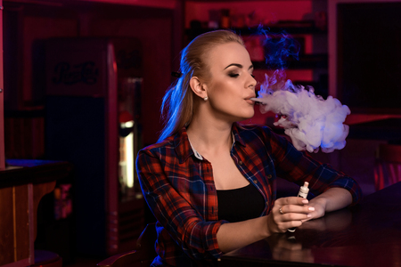 Young pretty woman in a shirt in a cage smoke an electronic cigarette at the vape bar