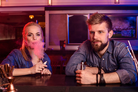A man and woman smoking electronic cigarette in a vape bar.