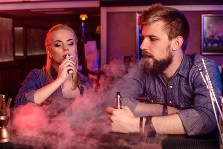 impersonal: A man and woman smoking electronic cigarette in a vape bar.