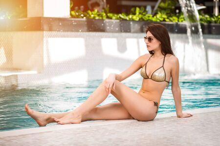 Woman in bikini sitting by the swimming pool