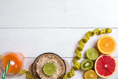 Fresh fruits with tape measure over white wooden background. Fitness concept. Flat lay. Top view. Copy space Stock Photo