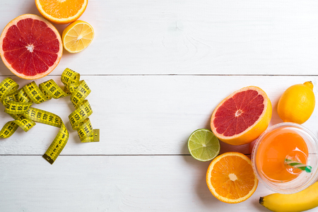 Fresh fruits with tape measure over white wooden background. Top view Stock Photo