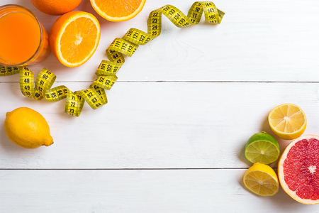 Fresh fruits with tape measure over white wooden background. Fitness concept. Top view. Copy space Flat lay Stock Photo