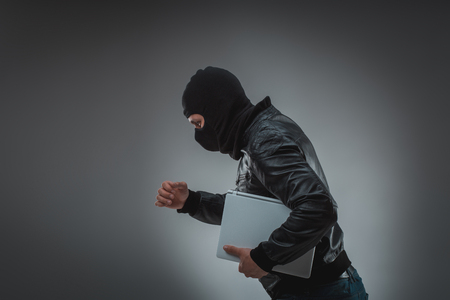 furtive: Thief stealing a laptop computer. Isolated on gray background Stock Photo