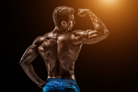Strong Athletic Man Fitness Model posing back muscles, triceps o