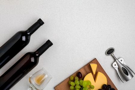 Glass of white wine, cheese and grapes. Top view Stock Photo