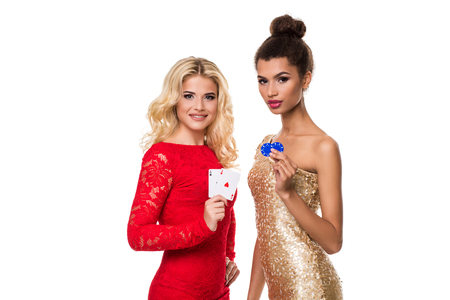 gamblers: Beautiful african woman and Caucasian young woman with long light blonde hair in evening outfit. Holding playing cards and chips. Isolated. Poker