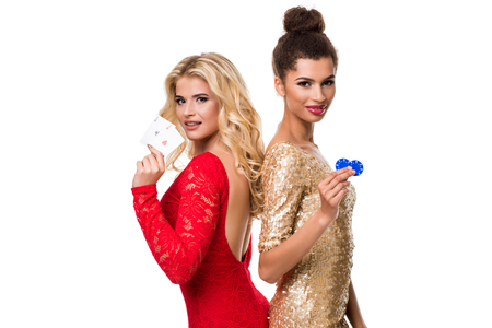 Beautiful african woman and Caucasian young woman with long light blonde hair in evening outfit. Holding playing cards and chips. Isolated. Poker