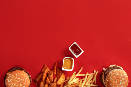 Fast food dish top view. Meat burger, potato chips and nuggets on red background. Takeaway composition. Top view