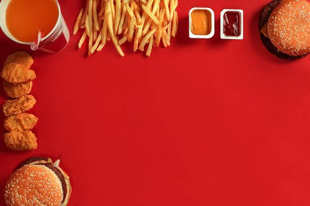 Fast food dish top view. Meat burger, potato chips and glass of drink on red background. Takeaway composition. Reklamní fotografie