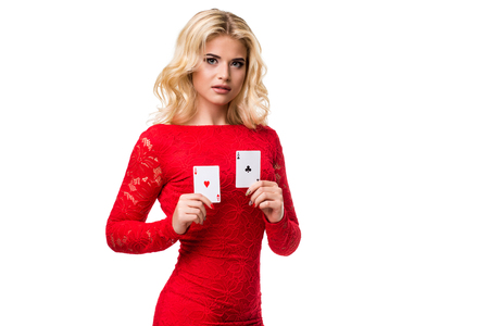 Caucasian young woman with long light blonde hair in evening outfit holding playing cards. Isolated. Poker Stock Photo