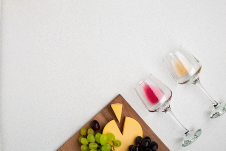 Two glasses of white and red wine, cheese and grapes. Top view