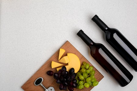 Two bottles of white and red wine, cheese and grapes. Top view