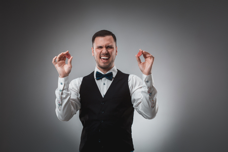 gamblers: A man holding up red poker chips. Poker