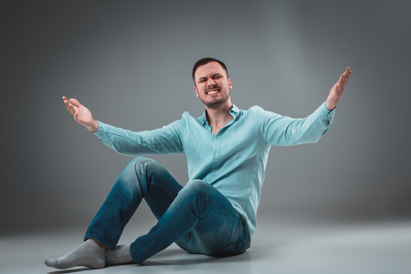 Handsome young man sitting on a floor with raised hands, isolated on gray background Stock Photo