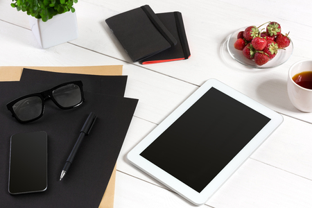 stockmarket: Modern workplace with digital tablet computer and mobile phone, cup of coffee, pen and empty sheet of paper.