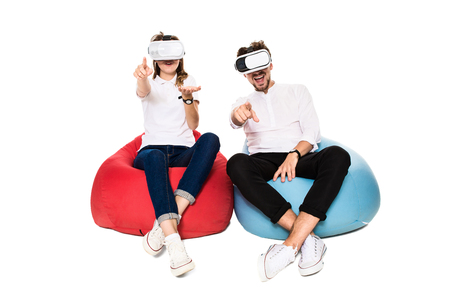 experiencing: Excited young couple experiencing virtual reality seated on beanbags isolated on white background