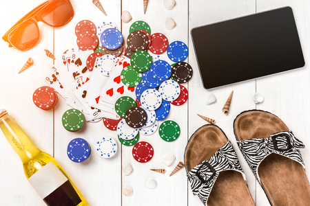 surrounded: Card deck surrounded by poker chips and scattered seashells on white wooden background with copy space Stock Photo