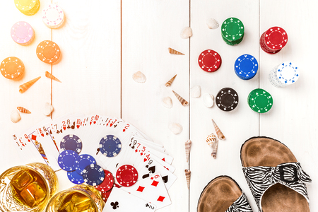 Card deck surrounded by poker chips and scattered seashells on white wooden background with copy space Stock Photo