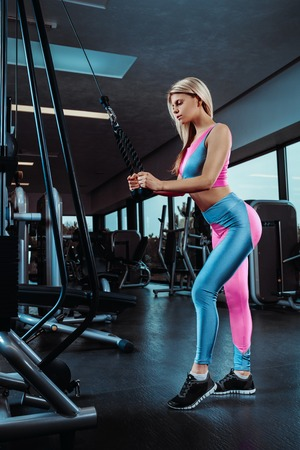 Young fitness woman execute exercise with exercise-machine in gym. Stock Photo