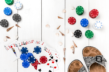 Gambling. Poker chips, cards and slippers on wooden table. Top view. Copyspace. Poker