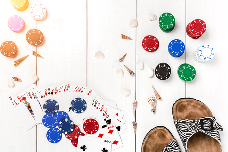 Gambling. Poker chips, cards and slippers on white wooden table. Top view. Copyspace. Poker.