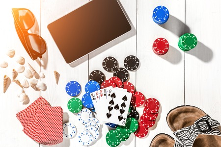 Gambling. Poker chips, cards and the dice nearby tablet on white wooden table. Top view. Copyspace. Poker. Summer. Sun flare