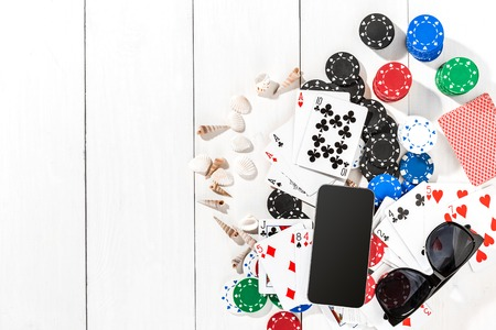 Gambling. Poker chips, cards, sunglasses and smart on white wooden table. Top view. Copyspace. Poker. Summer Stock Photo