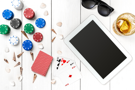 Gambling. Poker chips, cards and the dice nearby tablet on white wooden table. Top view. Copyspace. Poker. Summer Stock Photo