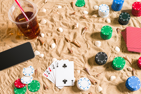 Gambling on vacation concept - white sand with seashells , colored poker chips and cards. Top view. Copy space. Summer