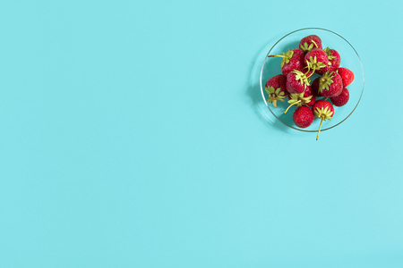 Ripe strawberries on the saucer isolated on mint background. Top view. Copy space. Still life mockup flat lay Stock Photo