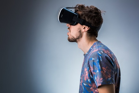 Side view of a young guy using a VR headset. Emotions