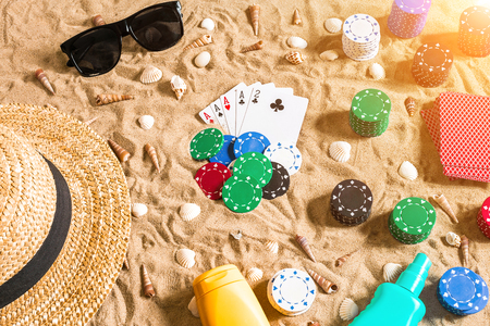 Beachpoker. Chips and cards on the sand. Around the seashells, sunglasses and hat. Top view. Copy space. Flat lay. Sun flare