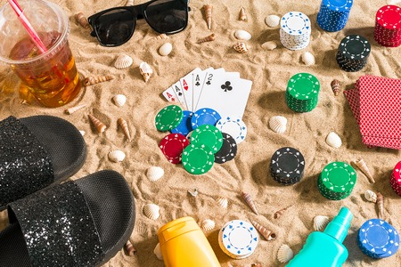 Beachpoker. Chips and cards on the sand. Around the seashells, sunglasses and flip flops. Top view. Copy space. Flat lay Stock Photo